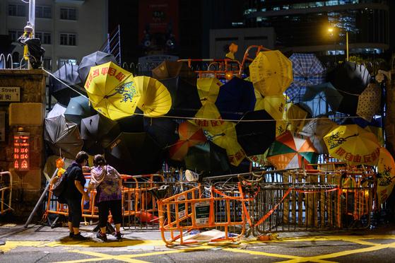 27일 새벽 시위대가 경찰본부 정문을 바리케이드와 노란 우산으로 봉쇄하고 있다.[AFP=연합뉴스]