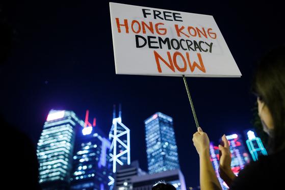 26일 밤 홍콩도심에서 한 시위대가 '자유 홍콩'과 '민주주의'라고 쓰인 푯말을 들고 있다.[로이터=연합뉴스]