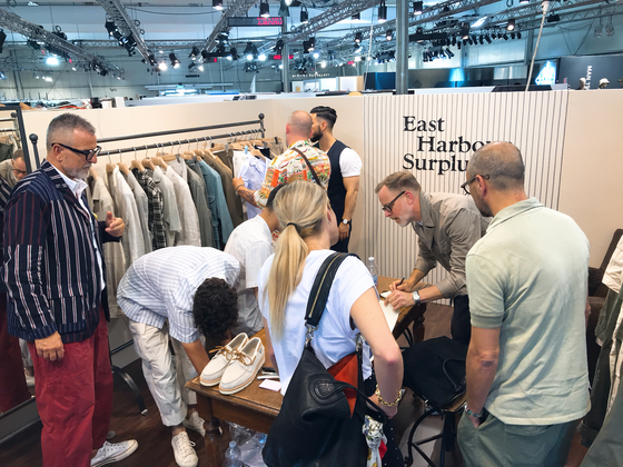 국내에서 편집숍 '샌프란시스코 마켓'을 운영하고 있는 한태민 대표가 선보인 브랜드 '이스트 하버 서플러스' 부스에서 버그도프 굿 맨 백화점의 남성복 바이어들이 모여 옷을 살펴보고 있다.