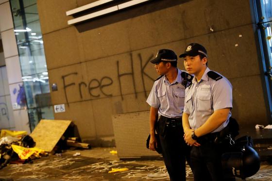 27일 새벽 경찰들이 경찰본부 앞에 서 있다. 뒤로 경찰본부 외벽에 시위대가 낙서한 글이 보인다.[연합뉴스]