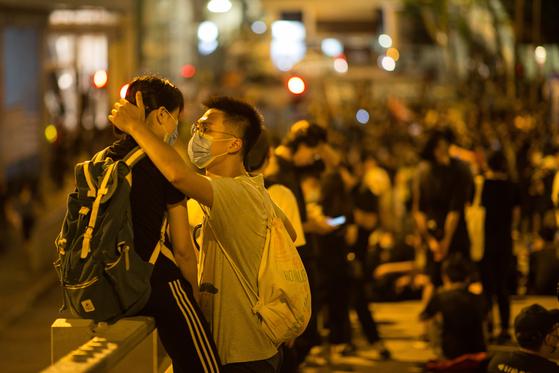 경찰본부 앞에서 26일 밤 자정을 넘겨 계속된 시위현장을 지키는 커플의 모습.[EPA=연합뉴스]