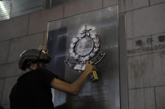 시위대가 26일 밤 경찰본부 앞 엠블럼에 낙서를 하고 있다.[AP=연합뉴스]