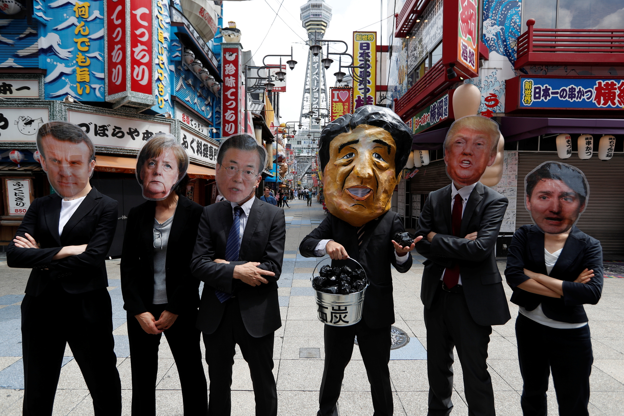 G20에 참가한 각국 정상들의 가면을 쓴 시위대가 28일 일본 오사카 시내에서 석탄화력 발전 사업에 대한 자금지원 중단을 촉구하는 시위를 하고 있다. 왼쪽부터 에마뉘엘 마크롱 프랑스 대통령, 앙겔라 메르켈 독일 총리, 문재인 대통령, 아베 신조 일본 총리, 도널드 트럼프 미국 대통령, 저스틴 트뤼도 캐나다 총리. [로이터=연합뉴스]