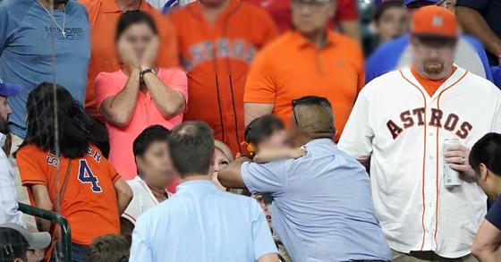 미국 텍사스주 휴스턴 미닛 메이드 파크에서 열린 2019 메이저리그(MLB) 시카고 컵스-휴스턴 애스트로스전 도중 컵스 타자 앨버트 알모라 주니어의 파울볼에 맞은 여자 어린이(가운데)가 한 남성에게 안겨 관중석을 빠져나가고 있다. [AP=연합뉴스]