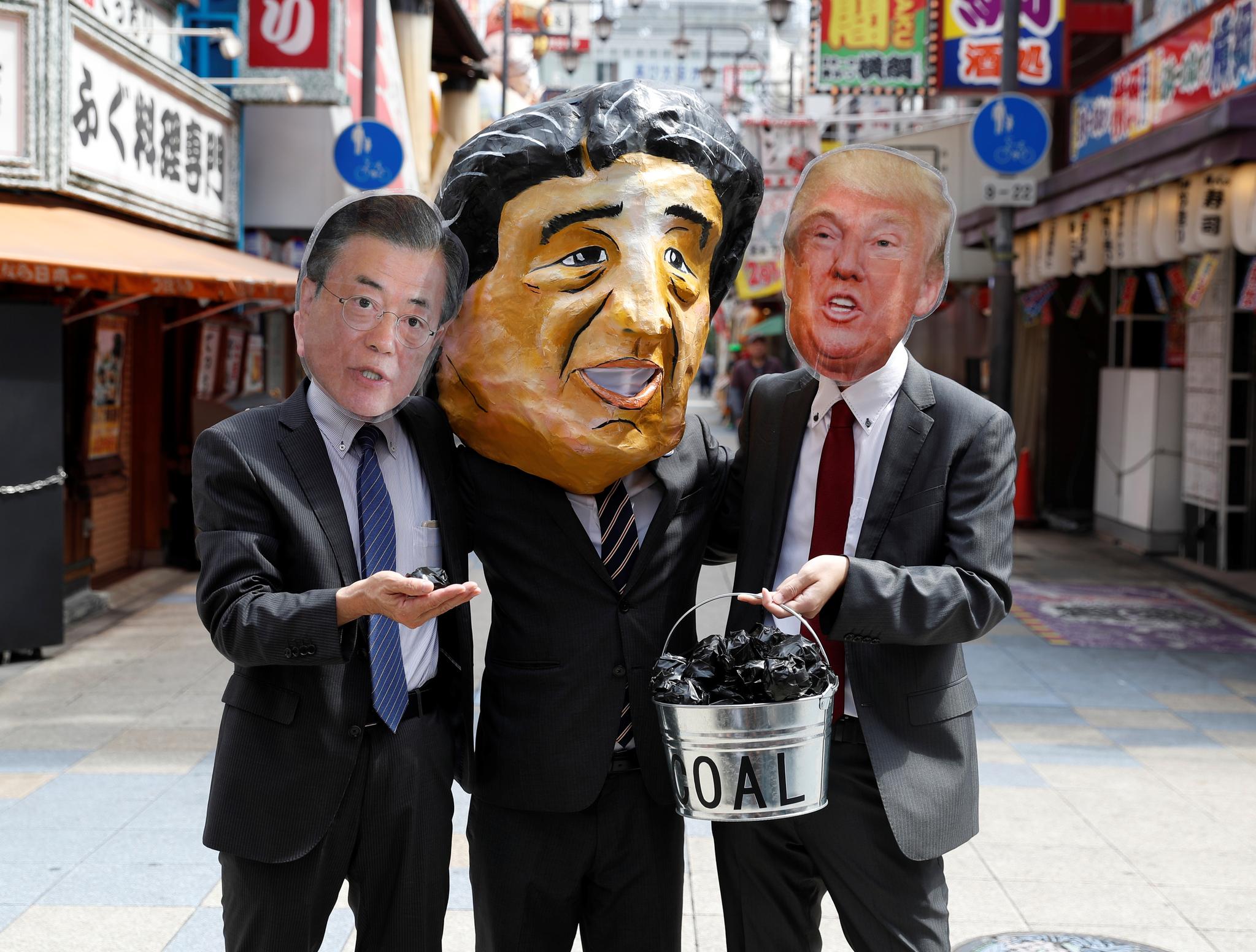 석탄을 손에 든 문재인 대통령과 아베 총리, 트럼프 대통령 가면을 쓴 시위대 모습. [로이터=연합뉴스]