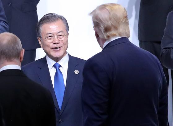 문재인 대통령이 28일 오전 오사카에서 열린 G20 정상회의 공식환영식에서 기념촬영 전 트럼프 미국 대통령과 인사하고 있다. [연합뉴스]