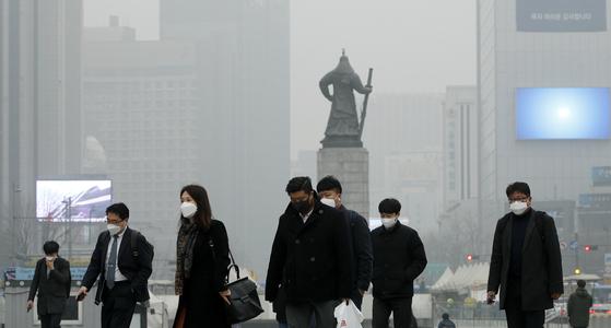 서울의 초미세먼지 농도가 세제곱미터당 160 마이크로그램까지 치솟으면서 역대 최고 수치를 기록한 지난 3월 5일 오전 광화문 광장에서 마스크를 쓴 시민들이 출근길을 서두르고 있다. [뉴스1]