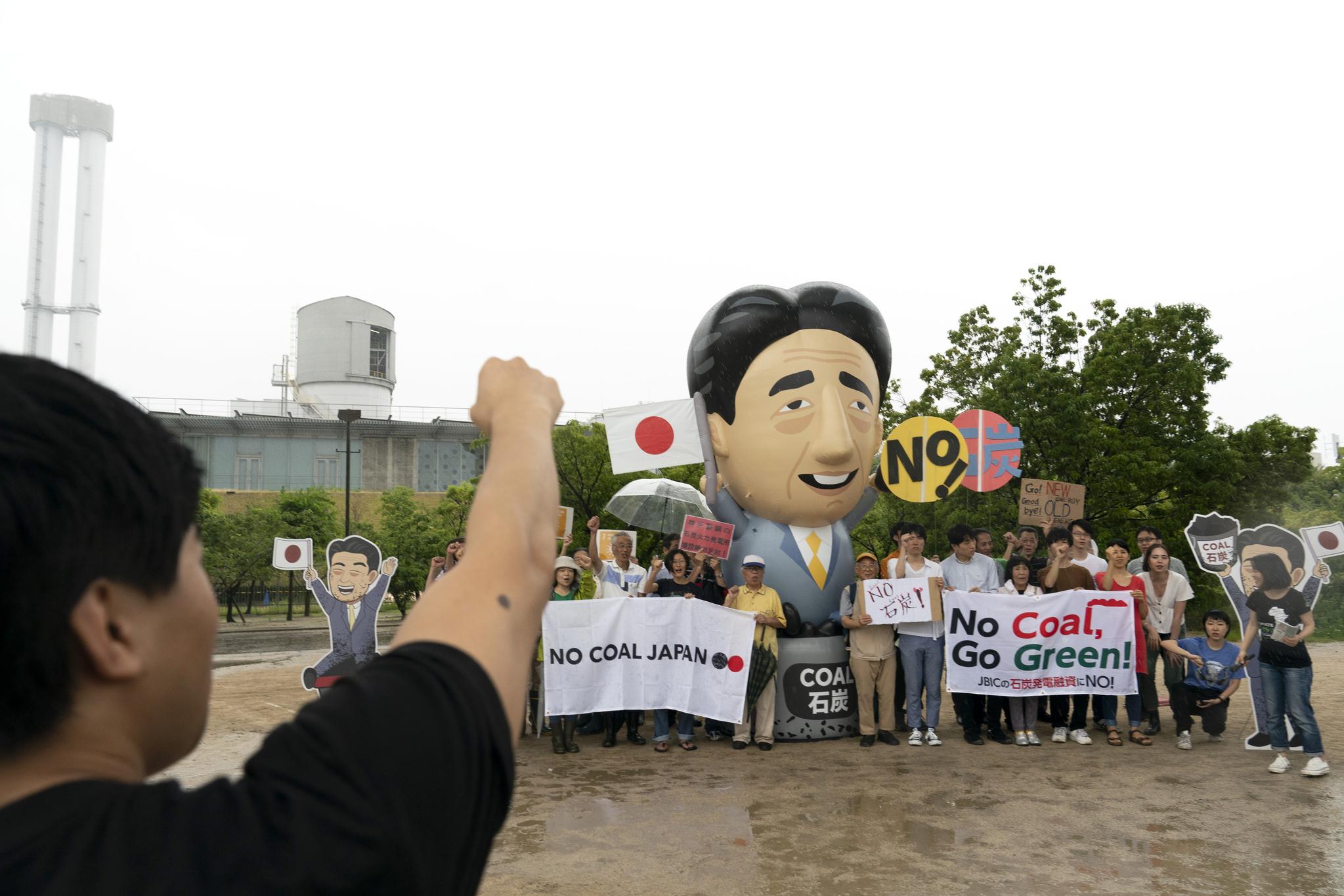 27일 일본 고베에서 환경운동가들과 지역주민들이 석탄 화력발전소 앞에 모여 아베 신조 일본 총리 풍선 인형을 세우고 구호를 외치고 있다. [AP=연합뉴스]