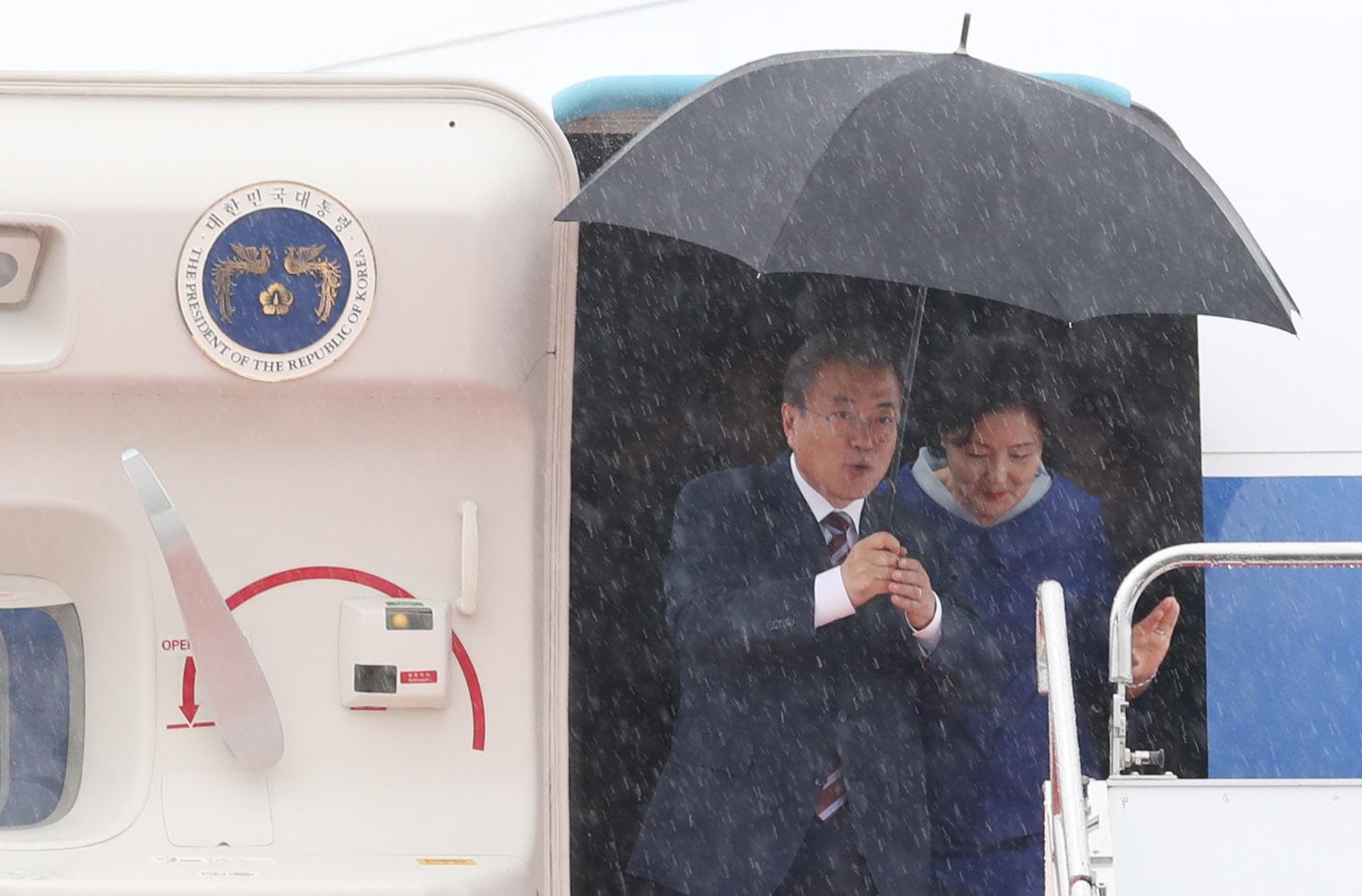 G20 정상회의에 참석하는 문재인 대통령과 김정숙 여사가 27일 오후 오사카 간사이 국제공항에 도착한 공군 1호기에서 내리고 있다. 비가 내려 문 대통령이 우산을 들고 있다. [연합뉴스]