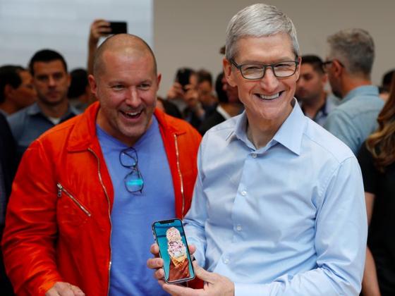 애플의 최고디자인책임자인 조너선 아이브(왼쪽)와 팀 쿡 CEO가 아이폰X 출시 이후 애플스토어 매장에서 즐거워하고 있다. [로이터=뉴시스]