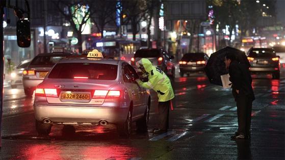경찰이 서울 시내에서 승차 거부 택시를 단속하고 있다.