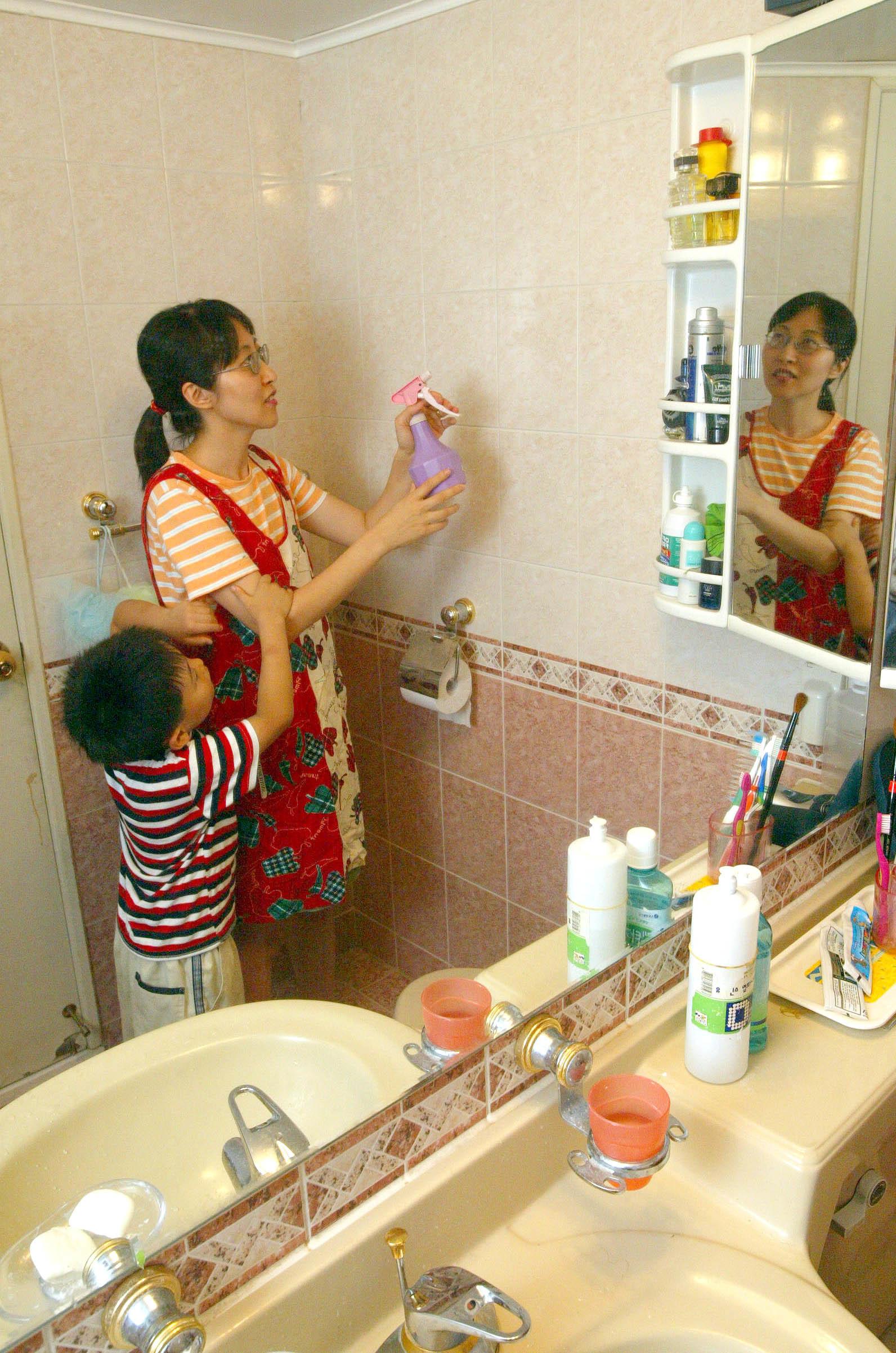 장마철 곰팡이가 자라지 않도록 물과 알코올을 혼합해 욕실 벽에 뿌리고 있다. [중앙포토]