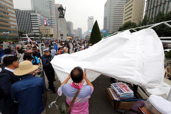 도널드 트럼프 미국 대통령의 방한을 하루 앞둔 28일 오전 우리공화당 당원들이 서울 광화문광장에 설치된 천막을 파이낸스센터 앞으로 옮기기 위해 철거하고 있다. [뉴스1]