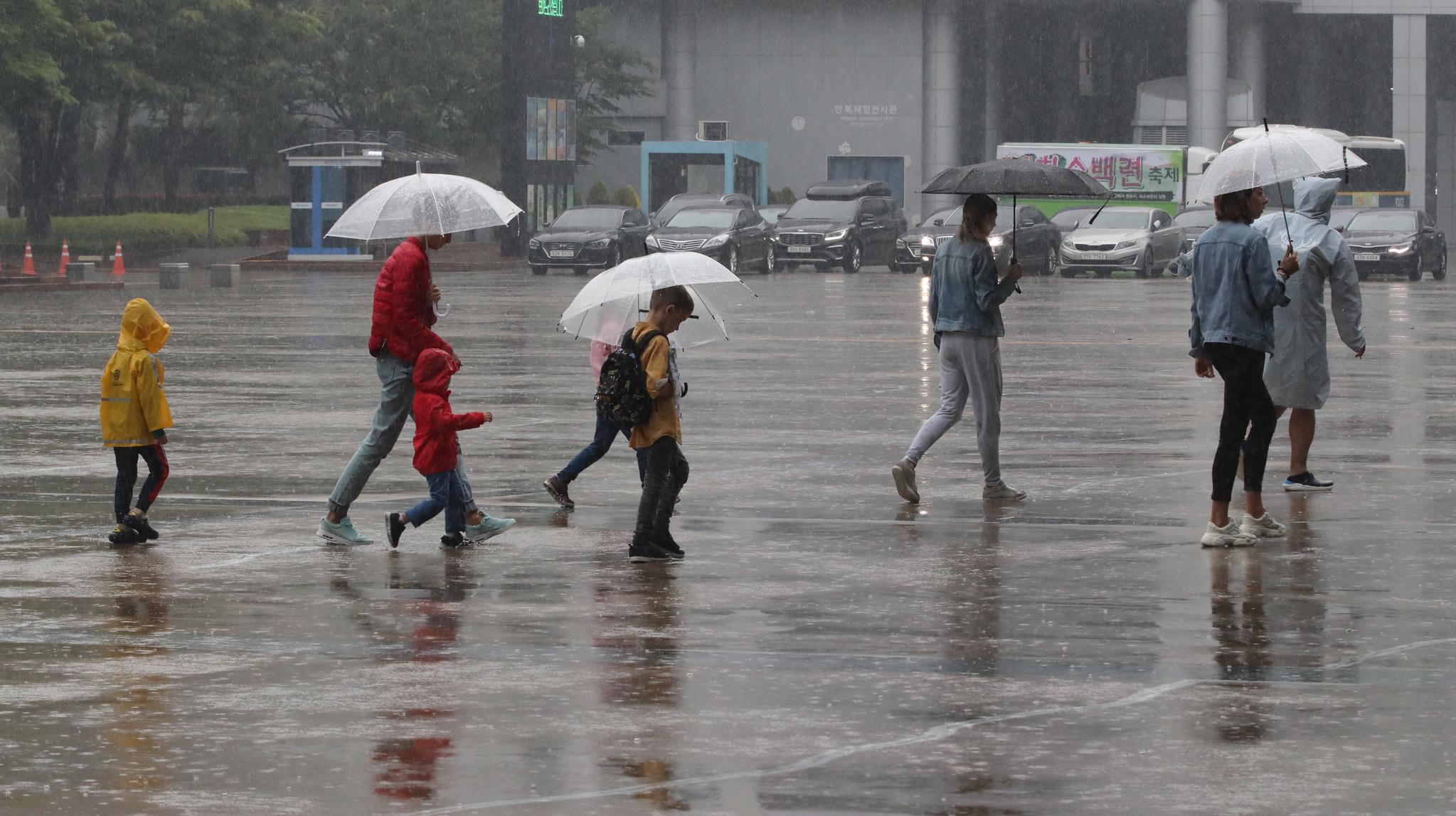 장마전선의 북상으로 부산지방에 호우주의보가 내려진 지난 26일 오후 부산 해운대구 벡스코를 찾은 관광객들이 우산을 쓴 채 광장을 지나고 있다. 송봉근 기자