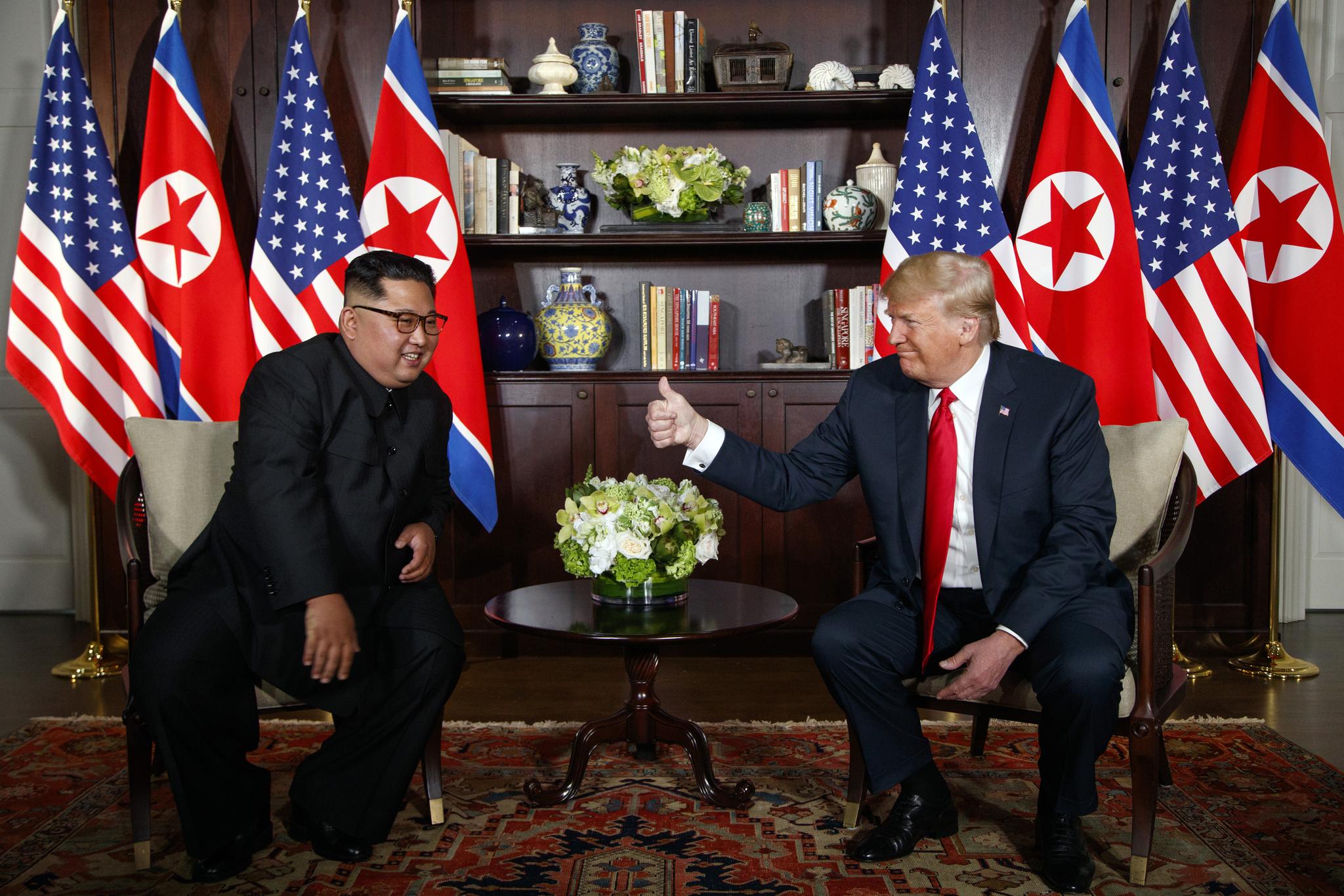 정상회담이 열린 12일 트럼프 대통령이 김정은 위원장과 나란히 앉아 엄지를 치켜세우고 있다. [AP=연합뉴스]