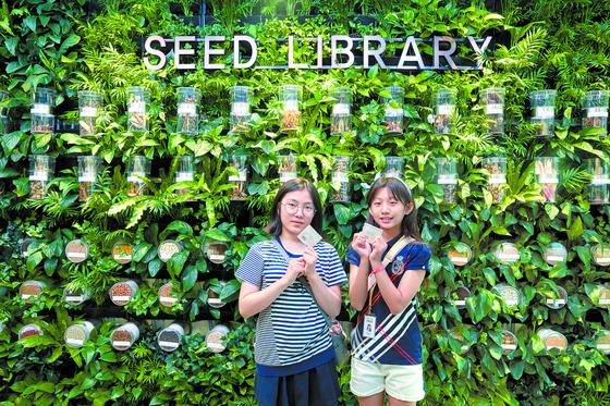 김수연(왼쪽)·정해린 학생기자가 서울식물원 내 씨앗도서관에서 대출한 씨앗 봉투를 들어 보였다.