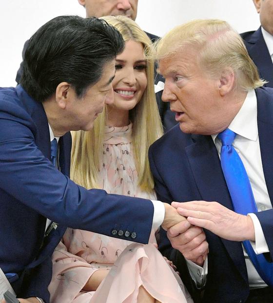 아베 신조 일본 총리(왼쪽)과 도널드 트럼프 미국 대통령(오른쪽)이 29일 일본 오사카에서 열린 주요 G20 정상회의의 특별 세션에서 트럼프 대통령의 딸 이방카를 사이에 두고 서로 손을 잡으며 대화를 나누고 있다. [연합뉴스]