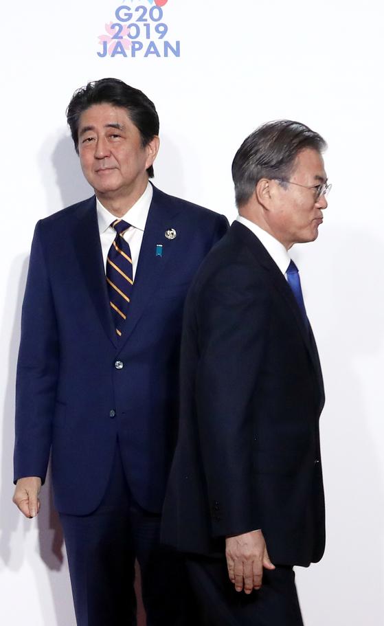 문재인 대통령(오른쪽)이 28일 오전 인텍스 오사카에서 열린 G20 정상회의 공식 환영식에서 의장국인 일본 아베 신조 총리와 인사한 뒤 이동하고 있다. [청와대사진기자단]