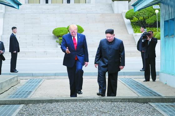 도널드 트럼프 미국 대통령과 김정은 북한 국무위원장이 30일 판문점 공동경비구역(JSA) 군사분계선 북측 지역에서 군사분계선 남쪽으로 넘어오고 있다. [청와대사진기자단]