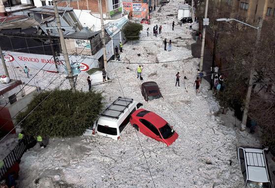 30일 새벽부터 온 우박과 빗물이 엉키면서 우박이 1m 높이로 과달라하라 도로에 쌓여 있다.[AFP=연합뉴스]