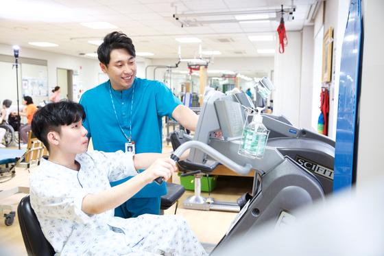 성인 뇌성마비 환자(왼쪽)가 보라매병원 재활치료실에서 운동치료를 받고 있다.[사진 보라매병원]