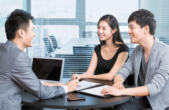 젊은 부부가 일찍부터 은퇴 후 노후 자금을 마련하기 위해 한 보험설계사와 상담하고 있다.