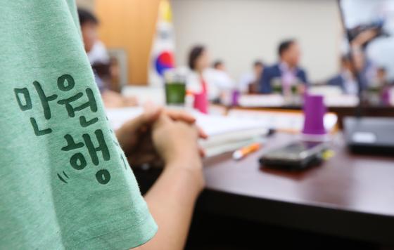근로자 위원인 이남신 한국비정규노동센터 소장이 지난달 25일 정부세종청사에서 열린 최저임금위원회 제4차 전원회의에 '만원 행동'이 적힌 티셔츠를 입고 있다. [연합뉴스]