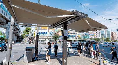 서울 광진구 구의동 자양사거리에 설치된 스마트 그늘막 아래로 주민들이 지나고 있다. [사진 광진구]