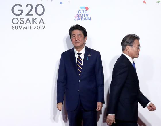 문재인 대통령이 지난달 28일 오전 인텍스 오사카에서 열린 G20 정상회의 공식환영식에서 의장국인 일본 아베 신조 총리와 악수한 뒤 이동하고 있다. [연합뉴스]