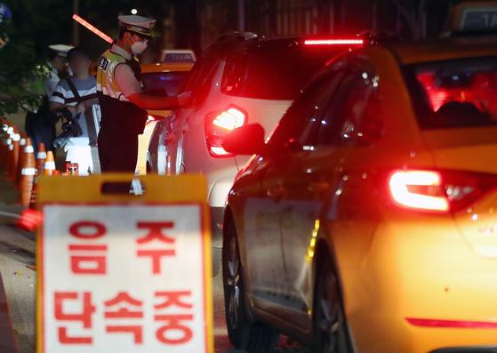 '제2윤창호법' 시행 첫 날인 지난달 25일 새벽 서울 마포구 합정역 인근에서 경찰이 음주운전 단속을 하고 있다. 이날 오전 0시부터 개정 도로교통법 시행에 따라 음주운전자에 대한 면허정지는 혈중알코올농도 0.05%에서 0.03%로, 면허취소는 0.10%에서 0.08%로 강화됐다. [뉴스1]