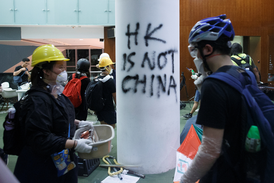 홍콩 시위대가 1일 밤 반정부 구호가 쓰여진 홍콩 입법회 건물 안을 지나고 있다.[로이터=연합뉴스]