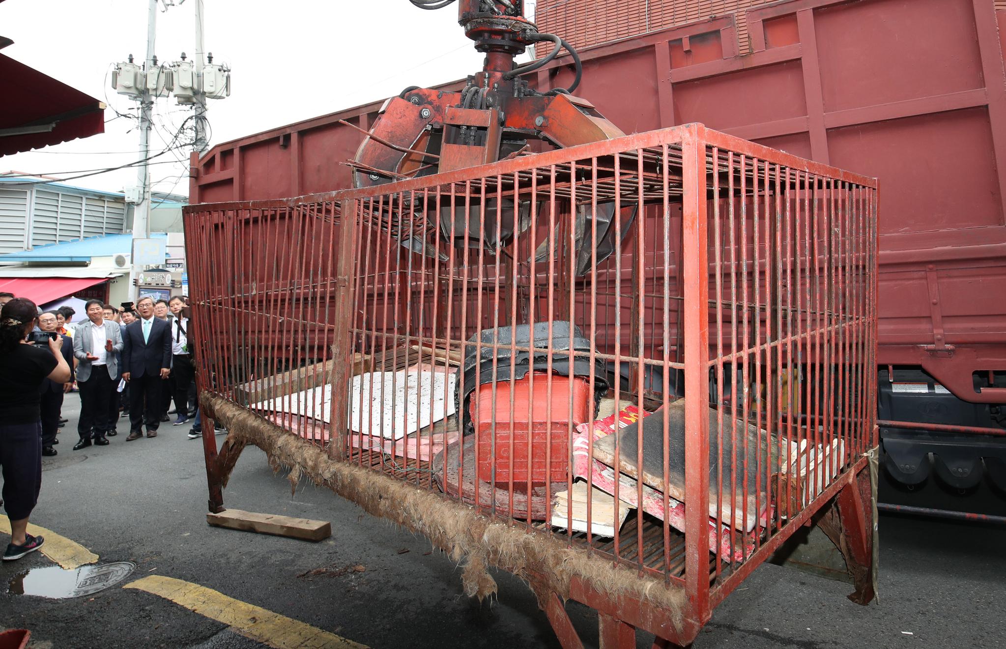 1일 오후 부산 북구 구포시장 내 가축시장에서 동물을 가두는 용도로 사용했던 철제 붉은색 우리가 철거되고 있다. 이날 구조된 반려동물들은 이 붉은색 우리에서 죽음을 기다리고 있었다.[뉴스1]