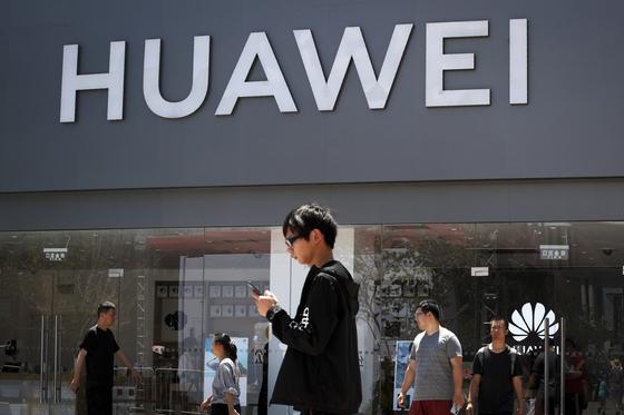 미국이 화웨이에 대한 제재 완화를 시사했다. 지난달 30일 중국 베이징의 화웨이 매장 앞을 행인들이 지나가고 있다. [AP=연합뉴스]