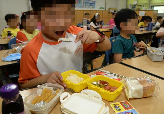 전국 학교 비정규직 노동자들이 파업을 실시한 3일 전북 전주시의 한 초등학생들이 학교에서 준비한 빵과 음료 그리고 학부모가 준비한 도시락을 책상에 꺼내놓고 점심을 먹고 있다. [뉴시스]