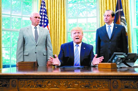"""도널드 트럼프 미국 대통령(가운데)이 1일(현지시간) 백악관에서 중미 이민자 급증에 대처하기 위한 연방정부 지원 예산안에 서명한 뒤 이야기하고 있다. 이날 트럼프 대통령은 김정은 북한 국무위원장과의 회동과 관련해 트위터에 '조만간 그를 다시 보기를 고대한다""""고 썼다. [AP=연합뉴스]"""