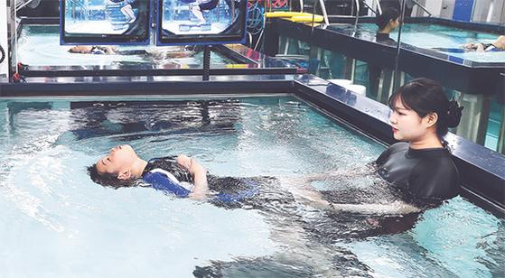 신경계 질환을 앓고 있는 환자가 2일 고양시 일산병원 재활센터에서 재활치료사의 도움을 받으며 수(水)치료를 받고 있다. [청와대사진기자단]