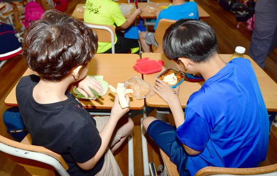 학교비정규직노조 총파업으로 광주?전남지역 300여개 학교에서 단체급식이 중단된 가운데 3일 오후 광주 서구 모 초등학교에서 학생들이 급식 대신 집에서 가져온 도시락과 지급 받은 빵과 음료수를 먹고 있다. [뉴시스]