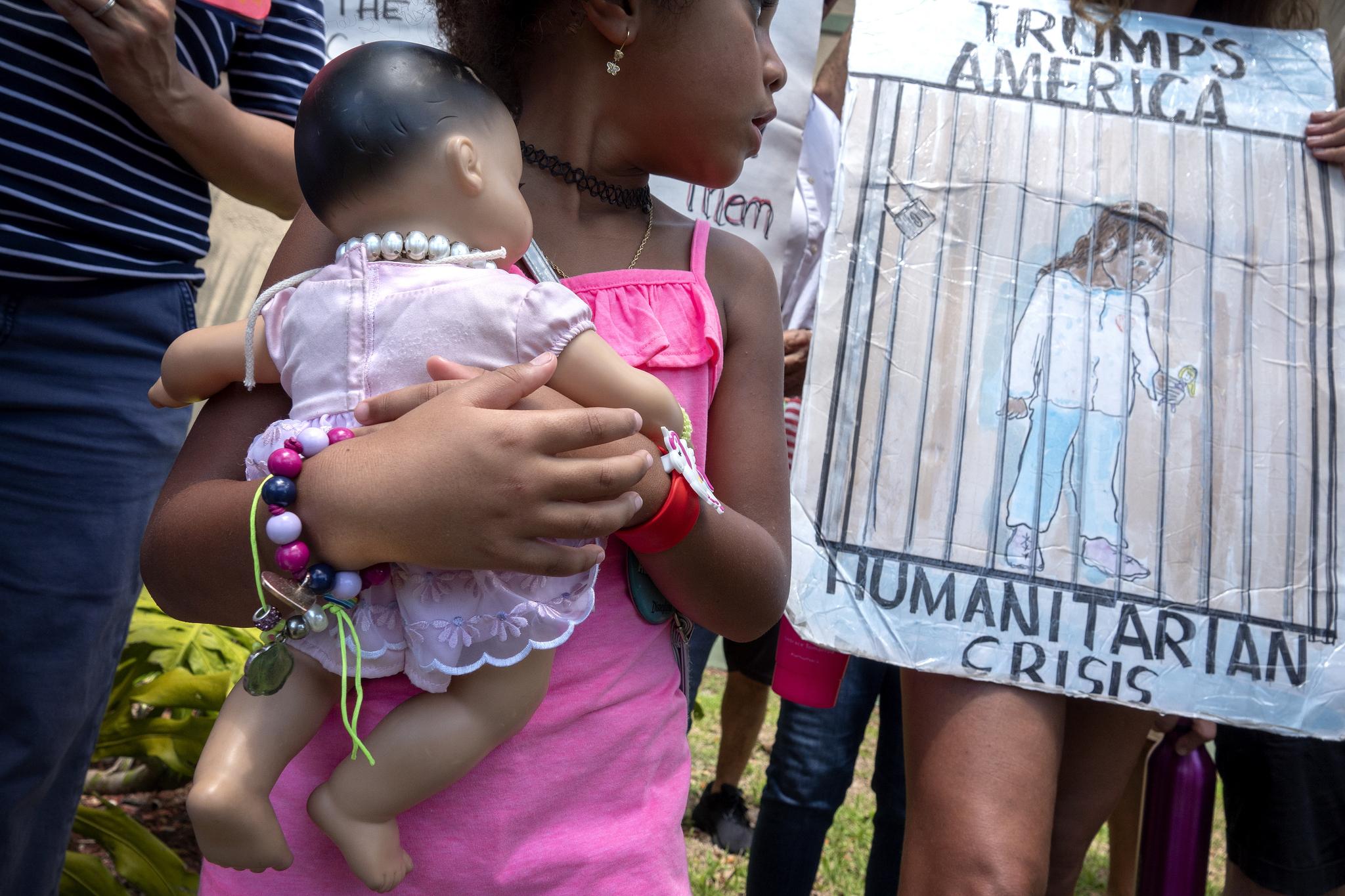 2일(현지시간) 미국 플로리다 주 마이애미에서 열린 미국 내 이민자 구금시설의 폐쇄를 주장하는 시위에서 한 소녀가 아기 인형을 들고 있다. 그의 우측편으로 구금시설에 수용된 이민자들의 모습을 그린 그림이 보인다. [로이터=연합뉴스]