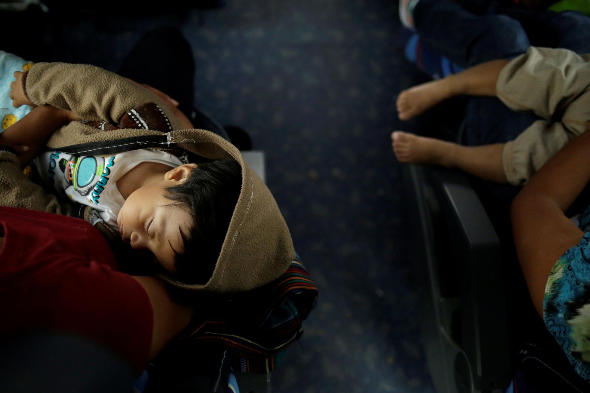 2일(현지시간) 열악한 환경을 견디다 못해 다시 멕시코로 돌아가는 길 을 선택한 이민자 아이들이 귀경 버스안에서 잠을 자고 있다. [로이터=연합뉴스]