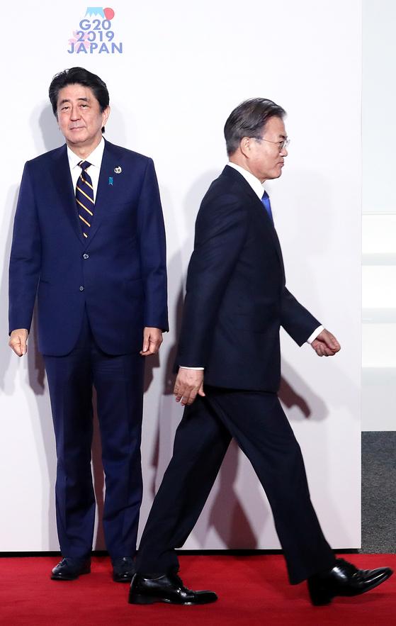 문재인 대통령(오른쪽)이 지난달 28일 일본 오사카에서 열린 G20 정상회의 환영식에서 아베 신조 일본 총리(왼쪽)와 8초간 악수한 뒤 이동하고 있다. [청와대사진기자단]