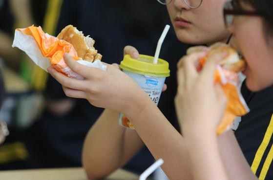 급식조리원 등 학교 비정규직 노동자들이 총파업에 들어간 첫날인 3일 오후 부산 연제구 한 여자중학교 학생들이 점심으로 햄버거와 과일 음료를 먹고 있다. [연합뉴스]