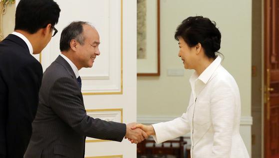 박근혜 대통령이 2016년 청와대에서 손정의 소프트뱅크 회장을 만나 악수를 하고 있다. [청와대사진기자단]