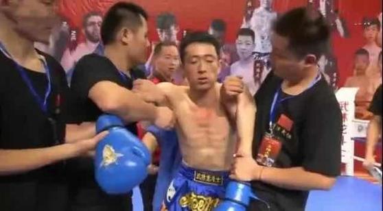 '점혈대사' 훠옌산의 일격을 받고 쓰러져 KO로 패한 중국식 격투기 싼다 선수 치웨이화가 세컨의 부축을 받아 일어나고 있다. [중국 환구망 캡처]