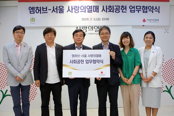 5일 사랑의열매회관에서 엠허브 추성호 대표이사(왼쪽에서 세 번째)와 서울 사랑의열매 김용희 사무처장(오른쪽에서 세 번째)이 협약식 기념촬영을 하고 있다.