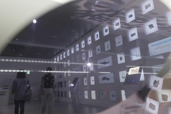 지난 1일 오후 서울 서초구 삼성전자 딜라이트 샵에 전시된 반도체 웨이퍼에 비친 전시품. 일본 정부는 4일부터 반도체·디스플레이·휴대폰에 들어가는 핵심 소제 3품목에 대한 수출 규제에 돌입했다. [연합뉴스]
