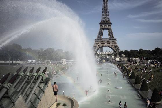 지난 6월 프랑스를 비롯한 유럽 곳곳에 최악의 폭염이 찾아왔다. 이 더위로 프랑스의 학교 4000여 곳이 휴교했고 산불이 났다. 사진은 사람들이 에펠탑 앞 분수에서 더위를 식히는 모습. [AP=연합뉴스]