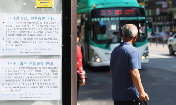 지난 1일부터 금융·버스운송·방송 등 21개 업종도 주52시간 근로제가 도입됐다. 사진은 1일 오후 경기도 안양시의 한 버스정류장에 주 52시간 단축 근로 시행에 따른 노선 폐지 안내문이 붙어 있는 모습. [연합뉴스]