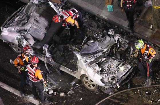 4일 오후 서울 서초구 잠원동 건물 외벽 붕괴 현장에서 119구조대원들이 매몰된 차량을 꺼내 조사하고 있다. [연합뉴스]