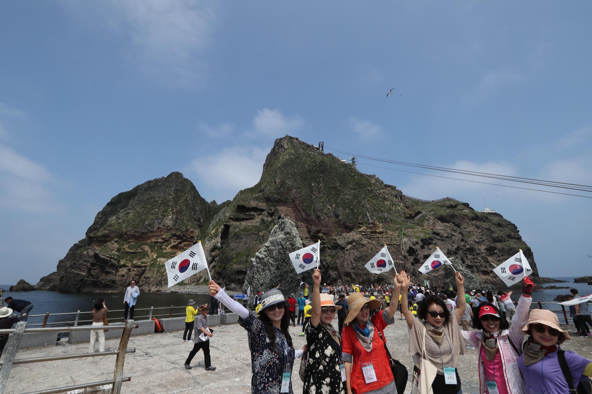 4일 오후 독도를 찾은 관광객들이 동도를 배경으로 태극기를 흔들며 기념사진을 찍고 있다. 독도=최승식 기자