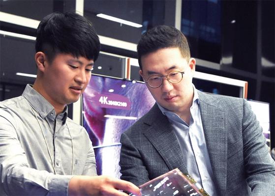 구광모 LG그룹 회장(오른쪽)이 서울 강서구에 있는 R&D 클러스터 'LG사이언스파크'에서 직원과 함께 OLED 신제품을 살펴보고 있다. 구 회장은 6월 29일로 취임 1주년을 맞았다. / 사진:LG그룹